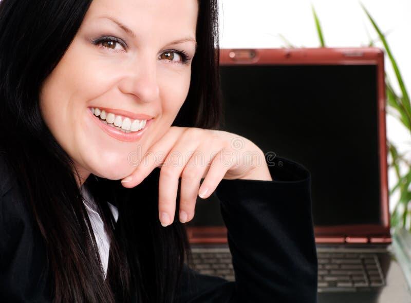Lächelnde Geschäftsfrau im Büro mit Laptop lizenzfreie stockfotos