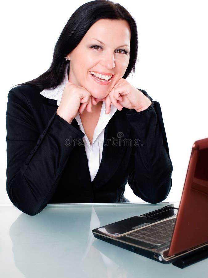 Lächelnde Geschäftsfrau im Büro mit Laptop stockfotos