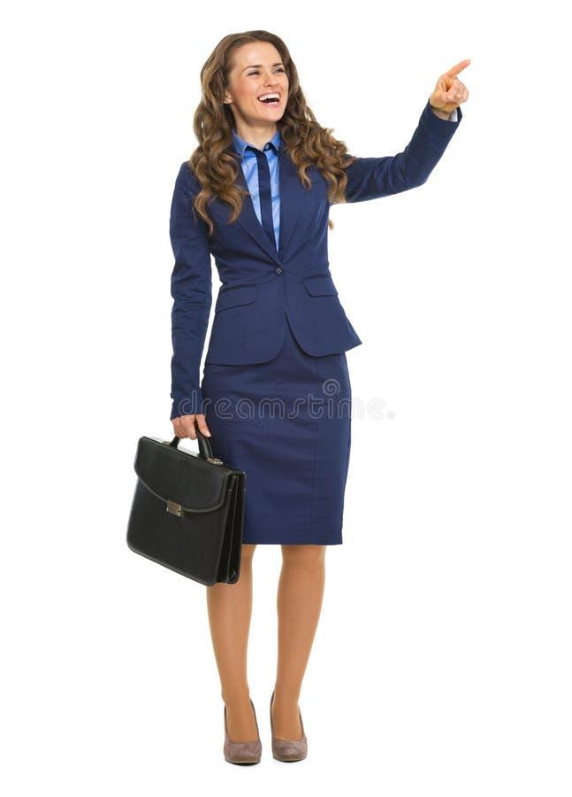 Lächelnde Geschäftsfrau mit Aktenkoffer zeigend auf Kopienraum lizenzfreies stockfoto