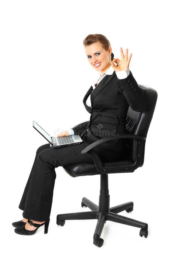 Lächelnde Geschäftsfrau mit dem Laptop, der o.k. darstellt stockbilder