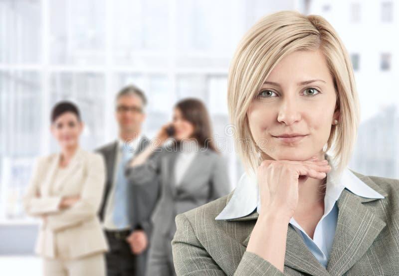 Lächelnde Geschäftsfrau mit Team stockbild