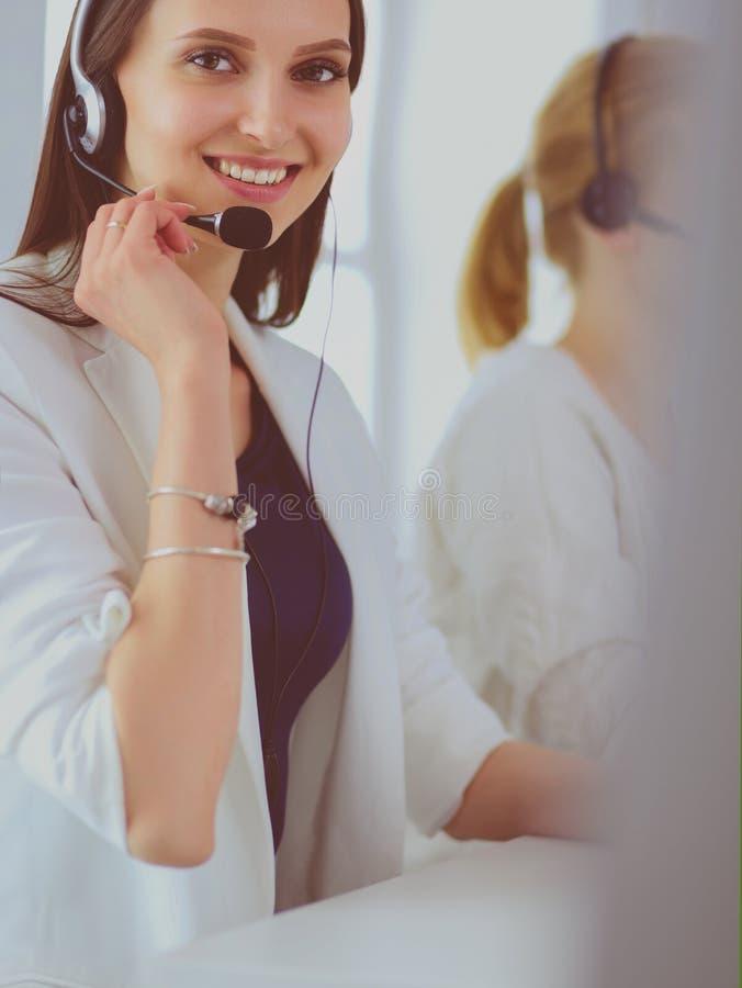 Lächelnde Geschäftsfrau oder Helpline-Bedienerin mit Headset und Computer im Büro lizenzfreie stockbilder