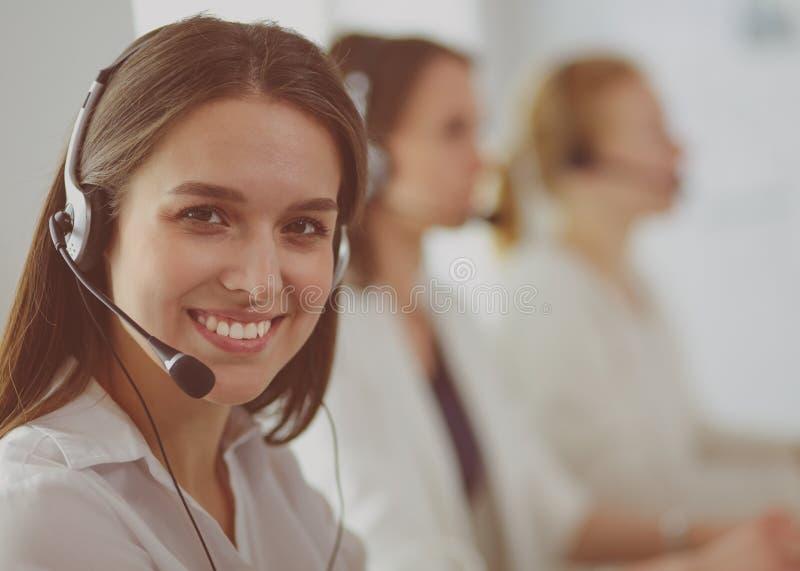 Lächelnde Geschäftsfrau oder Helpline-Bedienerin mit Headset und Computer im Büro stockbilder