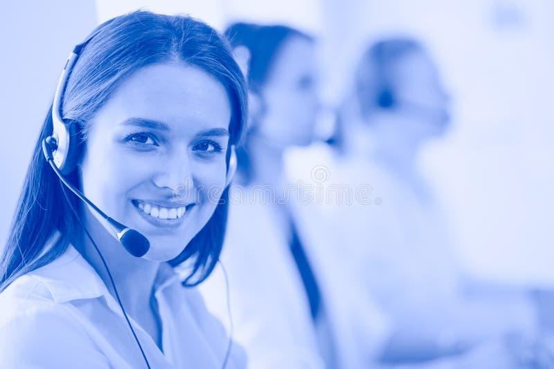 Lächelnde Geschäftsfrau oder Helpline-Bedienerin mit Headset und Computer im Büro stockfoto