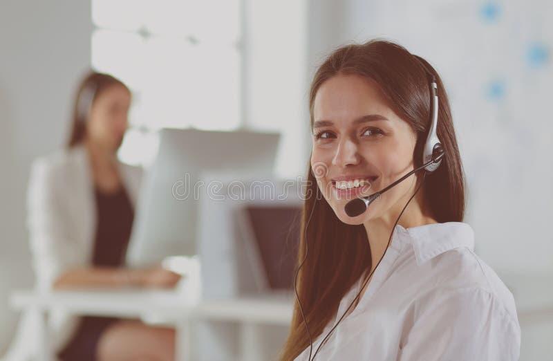 Lächelnde Geschäftsfrau oder Helpline-Bedienerin mit Headset und Computer im Büro stockfotos