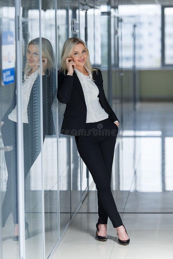 Lächelnde Geschäftsfrau am Telefon, das an voller Höhe und dem Betrachten der Kamera in einem Büro steht lizenzfreie stockfotografie
