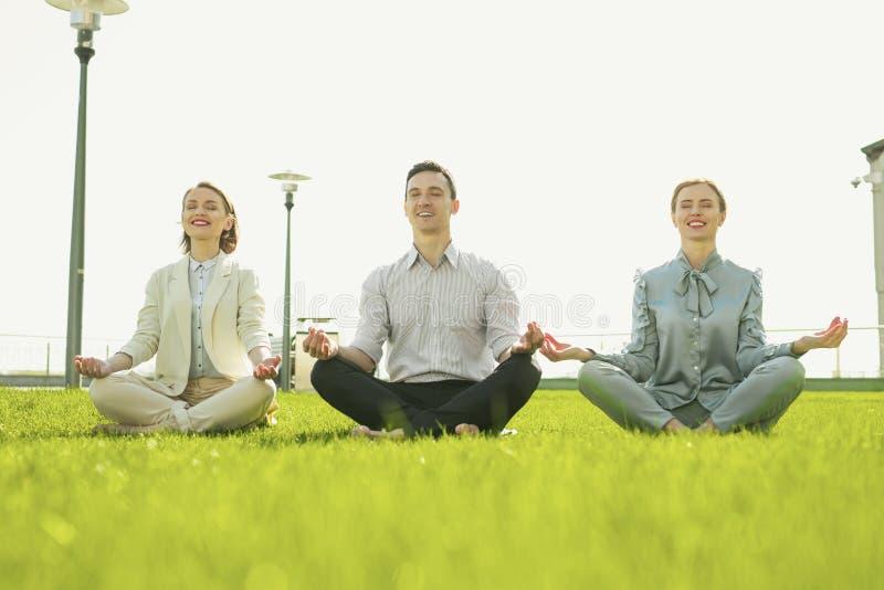 Lächelnde Geschäftskollegen, die Yoga auf Frischluft tun lizenzfreies stockfoto