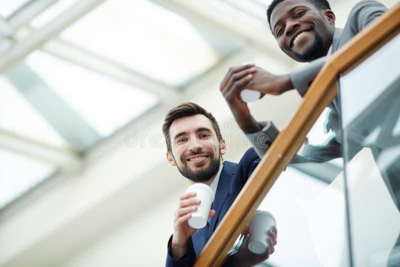 Lächelnde Geschäftsleute auf Bürogebäude-Balkon stockbild
