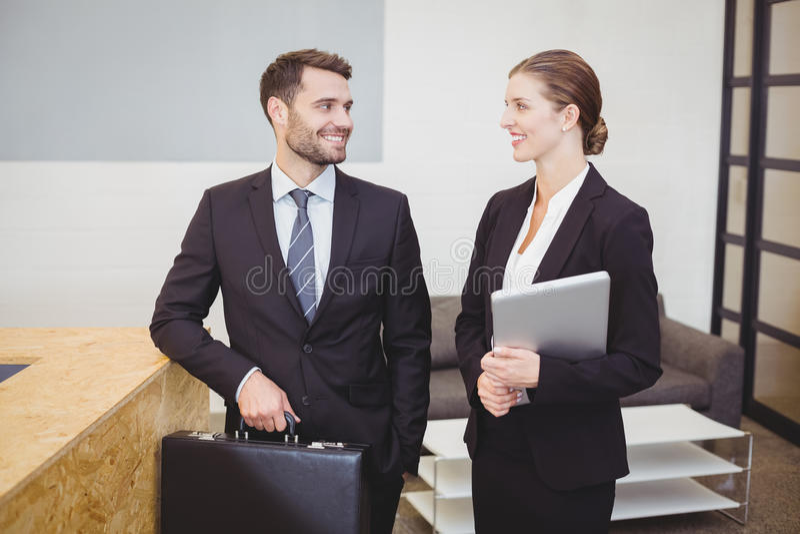 Lächelnde Geschäftsleute bei der Unterhaltung im Büro lizenzfreie stockfotos