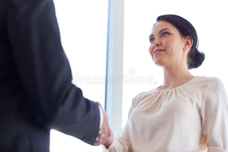 Lächelnde Geschäftsleute, die Hände im Büro rütteln stockfotos