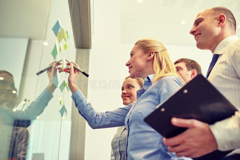 Lächelnde Geschäftsleute mit Markierung und Aufklebern stockbild