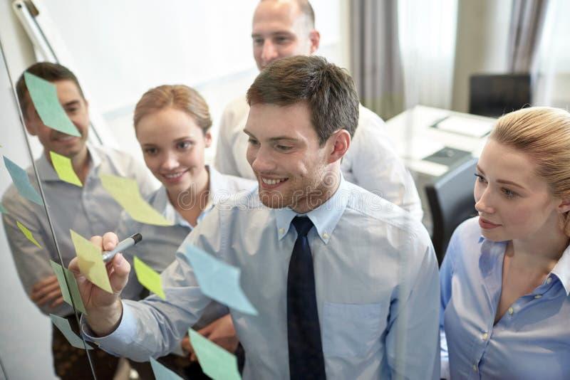 Lächelnde Geschäftsleute mit Markierung und Aufklebern lizenzfreies stockbild
