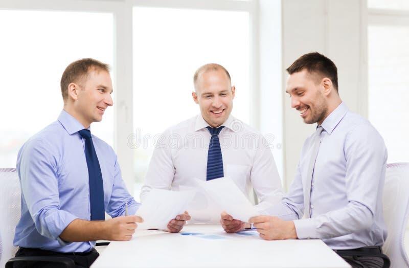 Lächelnde Geschäftsmänner mit Papieren im Büro stockbild