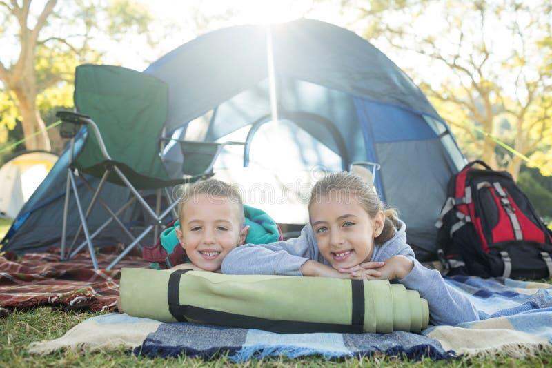 Lächelnde Geschwister, die außerhalb des Zeltes liegen stockfotos