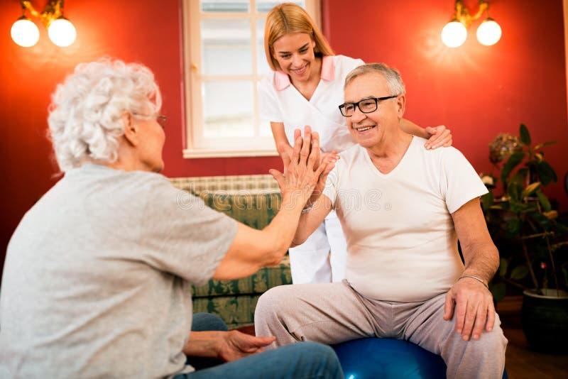 Lächelnde glückliche alte ältere Leute trainieren zusammen mit Krankenschwester stockbild