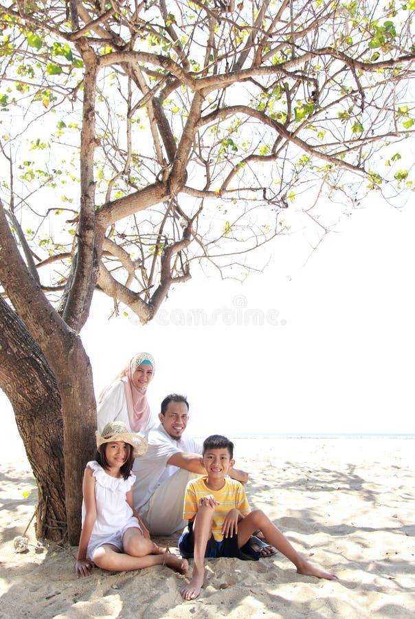Lächelnde glückliche Familie, die am Strand sich entspannt stockbild