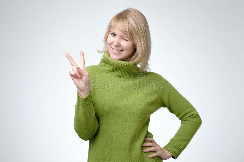 Lächelnde glückliche Frau freen herein Strickjackenvertretungssiegeszeichen und -c$betrachten der Kamera stockfoto
