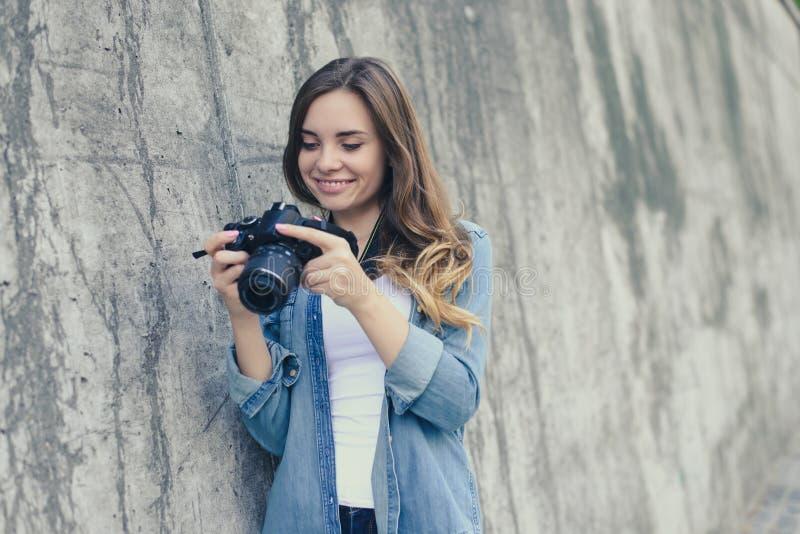 Lächelnde glückliche hübsche Frau, die Bilder auf ihrer Digitalkamera betrachtet Sie wird in der zufälligen Kleidung, graue Wand  stockfotografie