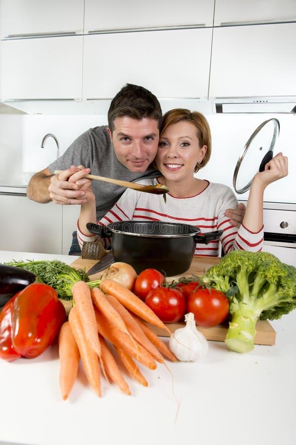 Lächelnde glückliche zusammen Frau der amerikanischen Küche der Paare zu Hause, die den Ehemann schmeckt das Gemüseeintopfgericht lizenzfreie stockfotos