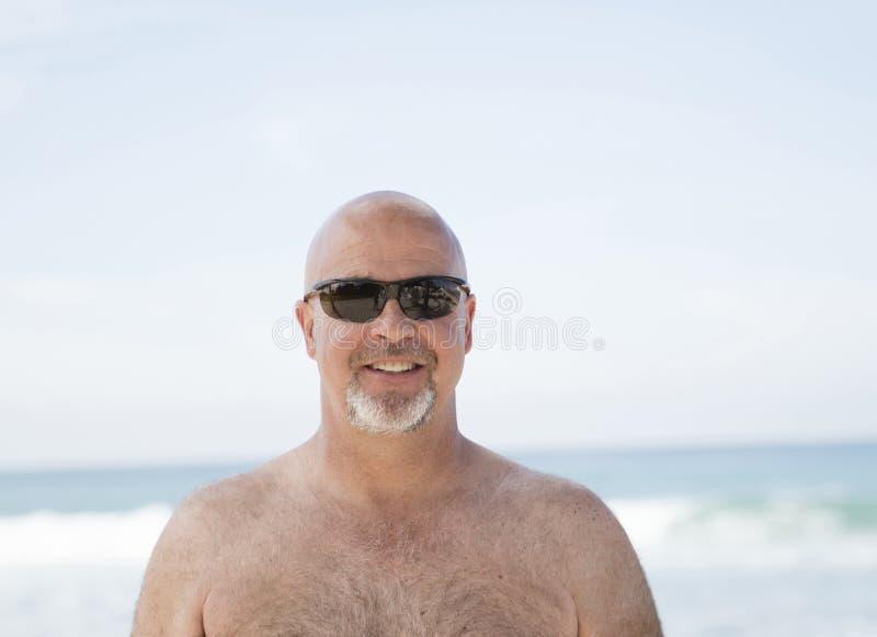 Lächelnde glücklicher kahler Mann-tragende Sonnenbrille auf dem Strand in Mexiko stockfotografie