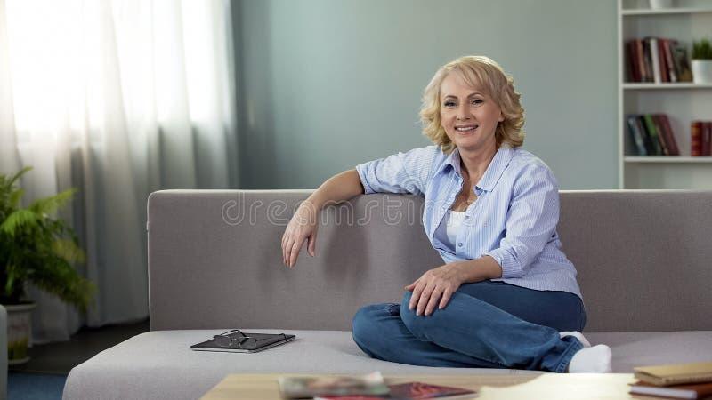 Lächelnde Greisin, die die Kamera, entspannend auf Sofahaus, weiblicher Pensionär untersucht stockfoto