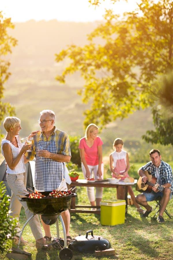 Lächelnde Großeltern, die Wein und das Genießen des Picknicks trinken stockfotos