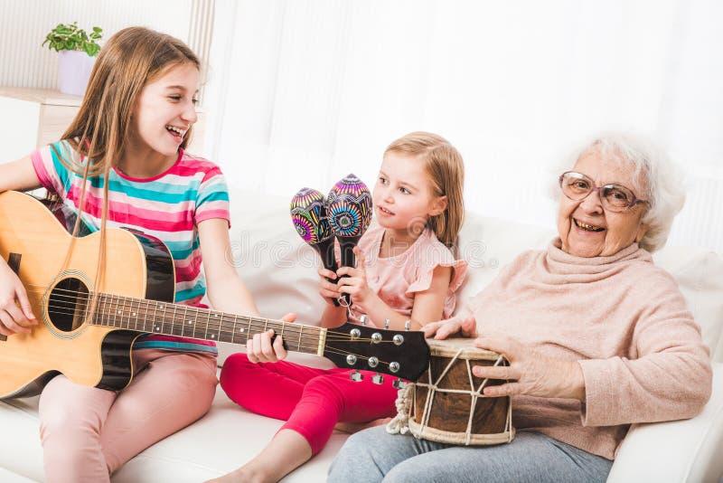 Lächelnde Großmutter mit den singenden Enkelinnen und Spielen stockfotos