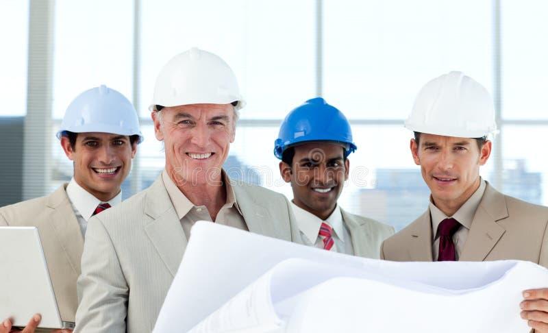 Lächelnde Gruppe überprüfenlichtpausen des Architekten lizenzfreies stockbild