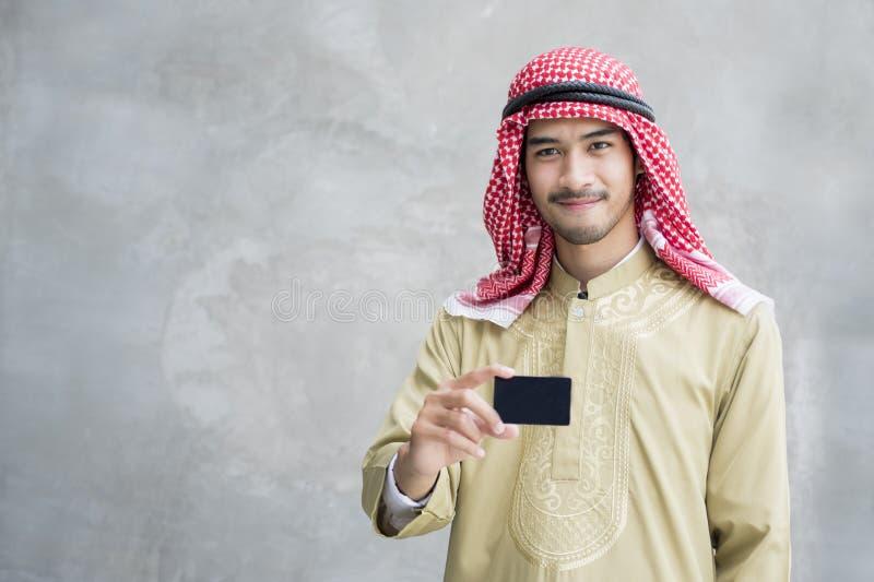 Lächelnde hübsche arabische Mannholdingvisitenkarte lizenzfreie stockfotografie