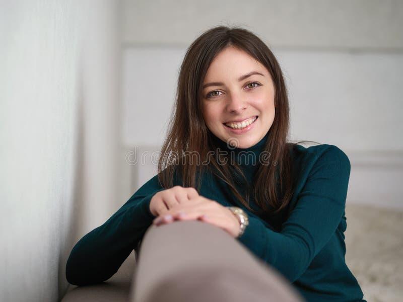Lächelnde hübsche brunette Frau mit ausgezeichneten Augen und entzückendes Lächeln in der grünen Strickjacke und in den Blue Jean lizenzfreies stockfoto