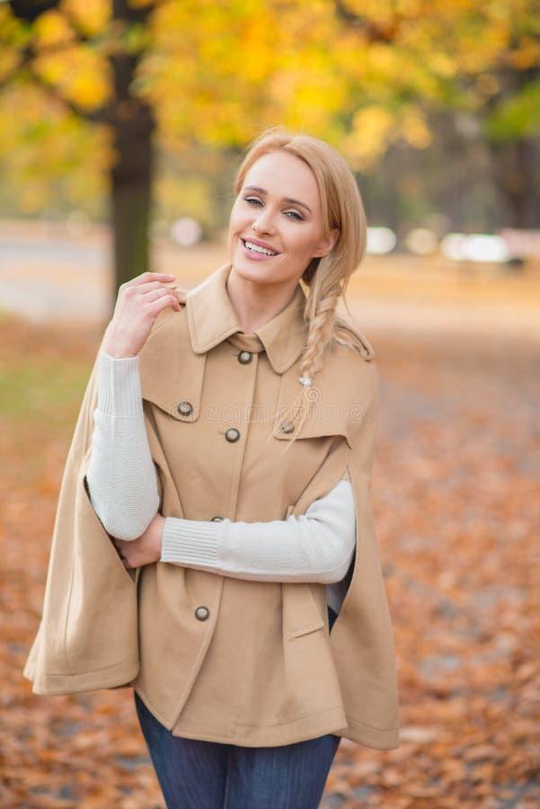 Lächelnde hübsche Frau in der Brown-Mode-Ausstattung stockfotos