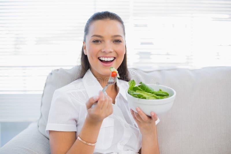 Lächelnde hübsche Frau, die den gesunden Salat sitzt auf Sofa hält lizenzfreies stockbild