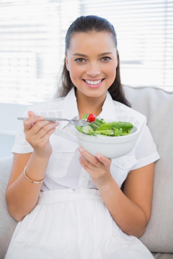 Lächelnde hübsche Frau, die den gesunden Salat sitzt auf Sofa isst stockfotos