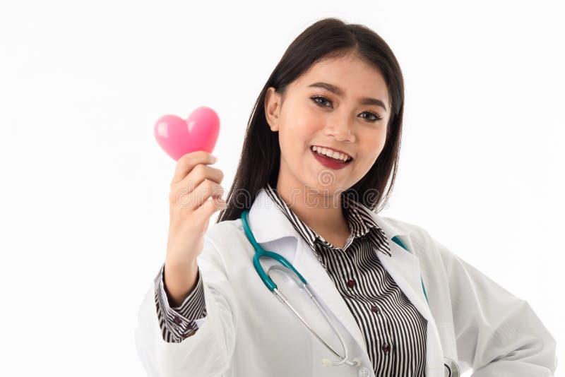 Lächelnde hübsche junge Ärztin, die rosa Herzformmodell hält stockfoto