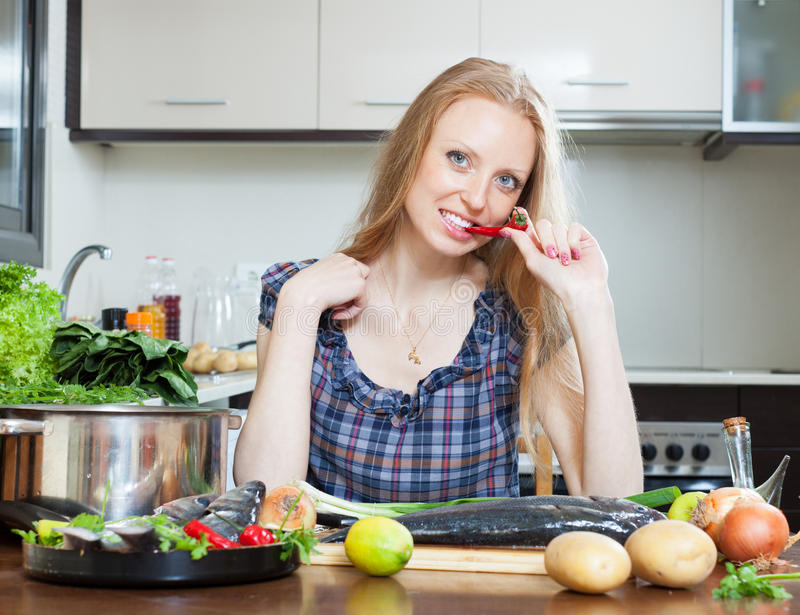 Lächelnde Hausfrau denkt, wie man Fische kocht stockfotos