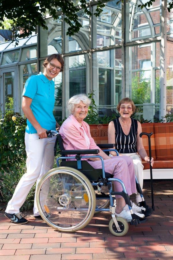 Lächelnde Heilberufler und ältere Personen stockfotos