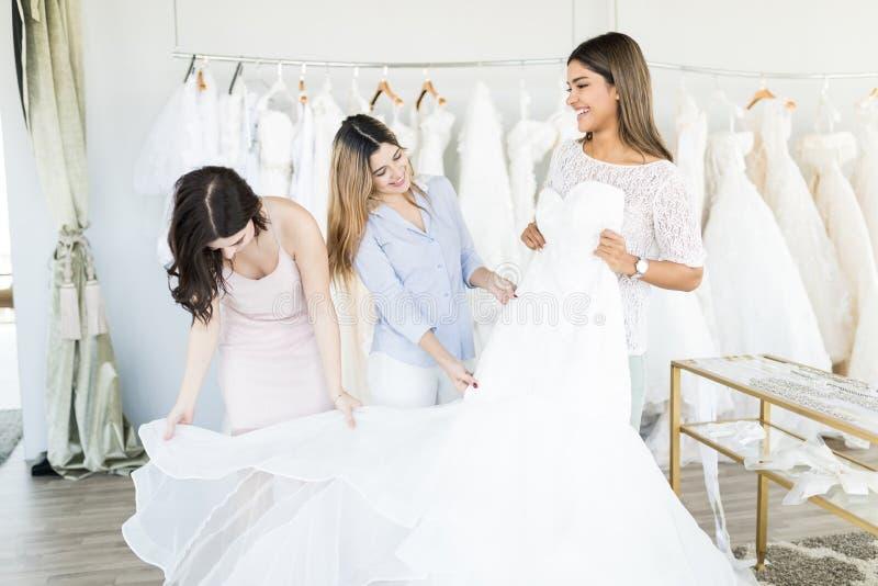 Lächelnde hispanische Braut, die elegantes Heirats-Kleid versucht stockfotos