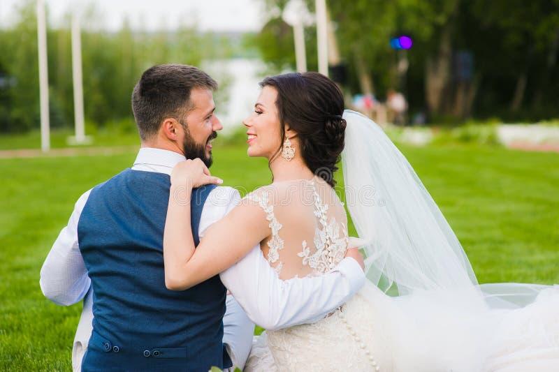 Lächelnde Hochzeitspaare von der Rückseite draußen stockbilder