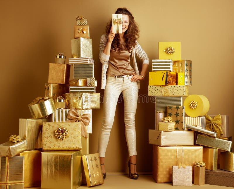 Lächelnde Holdinggeschenkbox der eleganten Frau, die sich halb vom Gesicht versteckt stockfotos