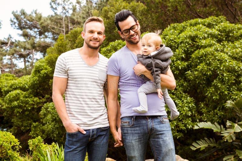Lächelnde homosexuelle Paare mit Kind stockbilder