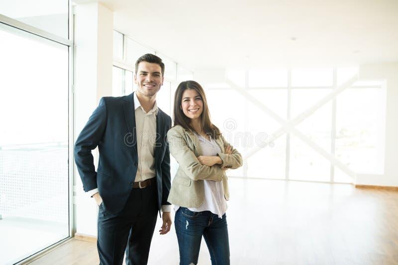 Lächelnde Immobilienagenturen, die in der neuen Wohnung stehen stockfotos