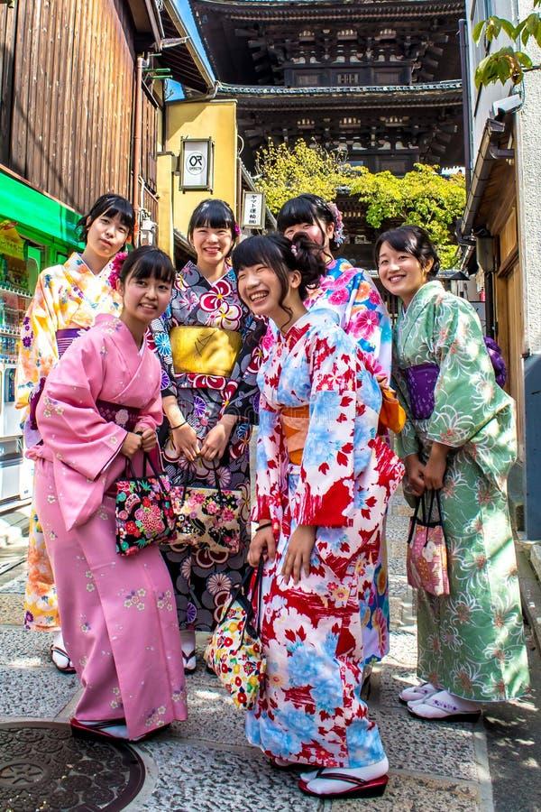 Lächelnde japanische Mädchen, die traditionellen Kimono tragen lizenzfreie stockfotografie