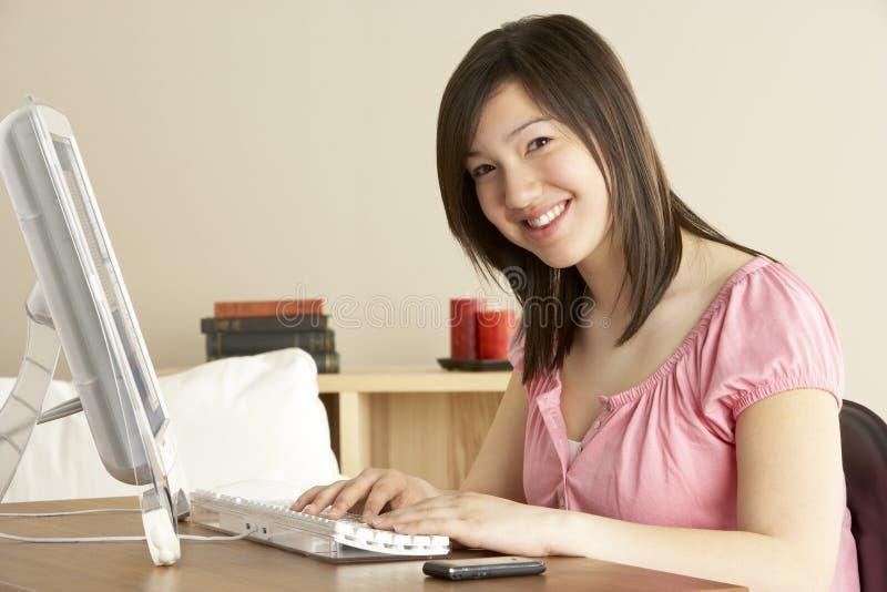 Lächelnde Jugendliche auf Computer zu Hause lizenzfreies stockfoto
