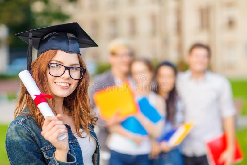 Lächelnde Jugendliche in der Eckekappe mit Diplom stockfoto