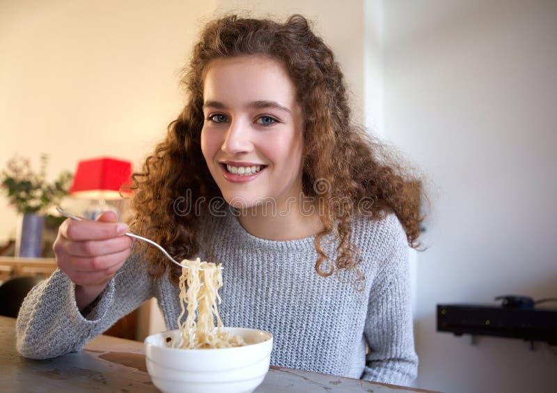 Lächelnde Jugendliche, die zu Hause Lebensmittel isst stockbild