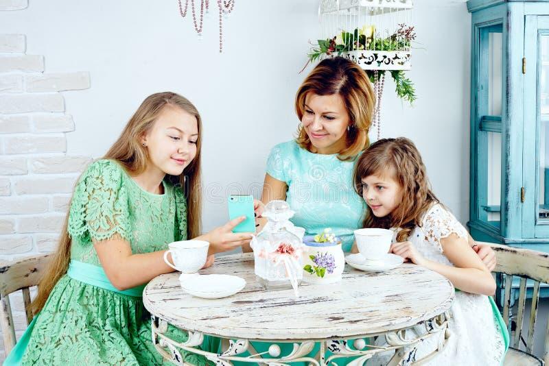 Lächelnde jugendliche Tochter, die der Mutter und der Schwester Fotos zeigt stockbild