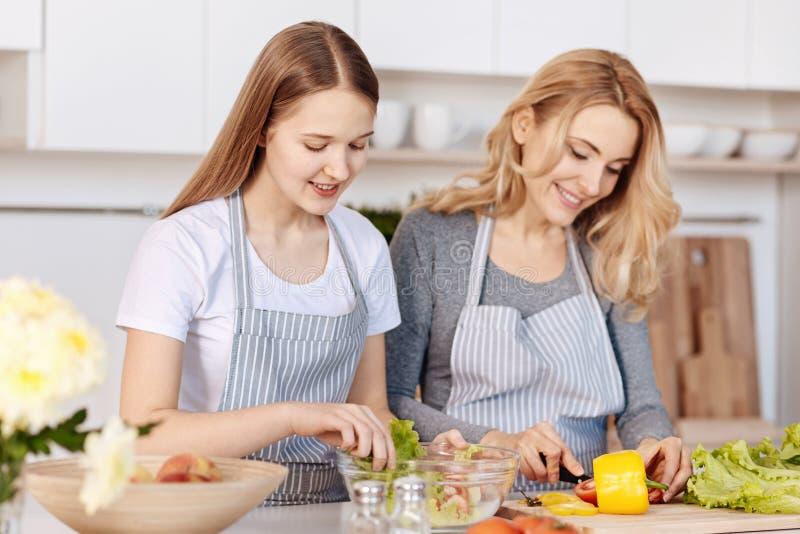Lächelnde Jugendliche und ihre Mutter, die auf der Küche kochen stockfotografie