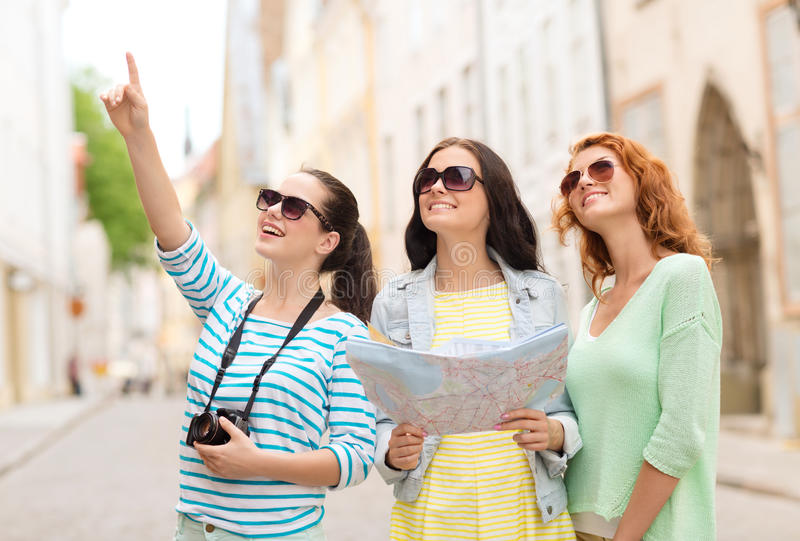 Lächelnde Jugendlichen mit Karte und Kamera stockfotos