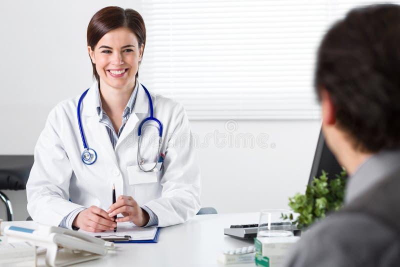 Lächelnde junge Ärztin, die auf Patienten hört lizenzfreie stockbilder