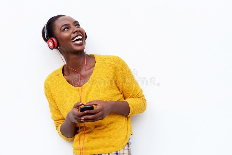 Lächelnde junge afrikanische Frau, die Musik mit Kopfhörern und Handy gegen lokalisierten weißen Hintergrund hört stockbild